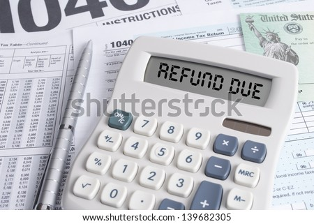 Tax Forms and Check with Calculator that spells out REFUND DUE on the display - stock photo