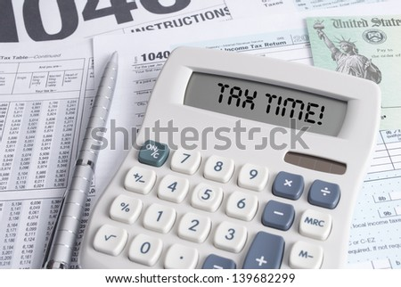 Tax Forms and Check with Calculator that spells out TAX TIME on the display - stock photo