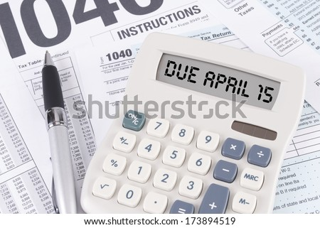 Tax Forms and Pen with a Calculator that spells out DUE APRIL 15 on the display - stock photo