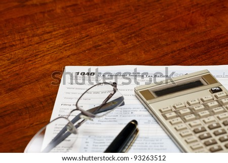 Tax forms, glasses, calculator and a pen on a desk ready for tax season
