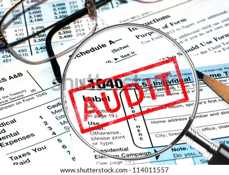 Tax forms under magnifying glass revealing an audit