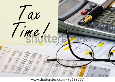 Tax forms with pen, calculator, glass and sticker.