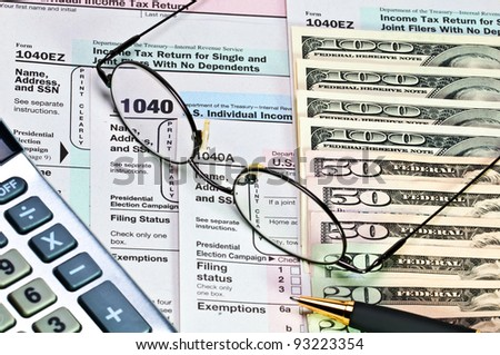 Tax forms 1040 with pen, glasses, calculator and money.