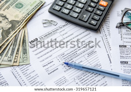 tax forms 1040 with the glasses, money and the pen - stock photo