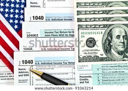 Tax forms 1040 with U.S. flag, pen and money.