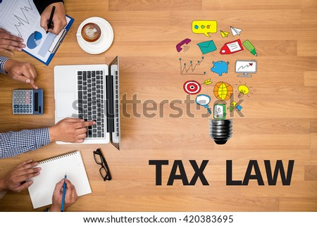 TAX LAW                Business team hands at work with financial reports and a laptop - stock photo