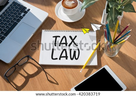 TAX LAW                open book on table and coffee Business - stock photo