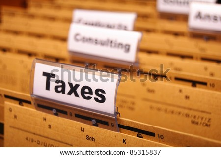 tax or taxes concept with word on business folder index - stock photo