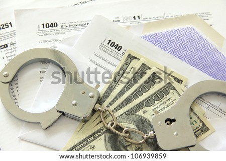 Tax papers in an envelope with dollar bills and handcuffs - stock photo