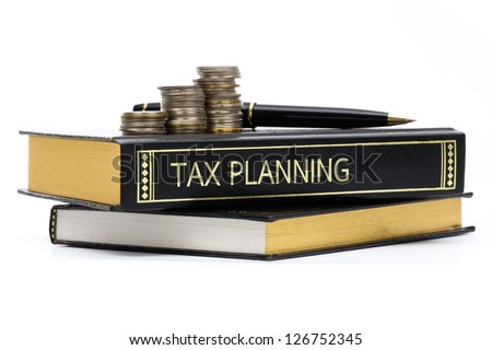 Tax planning book with coins and pen isolated on white - stock photo