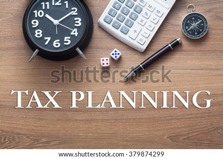 Tax Planning words written on wooden table with clock,dice,calculator pen and compass - stock photo