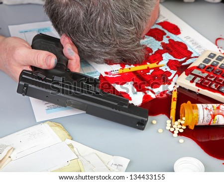 Tax Relief Gets Radical/Man's head laying against desktop covered with blood, IRS forms, a calculator, spilled pills & vial, & handgun on white desktop - stock photo