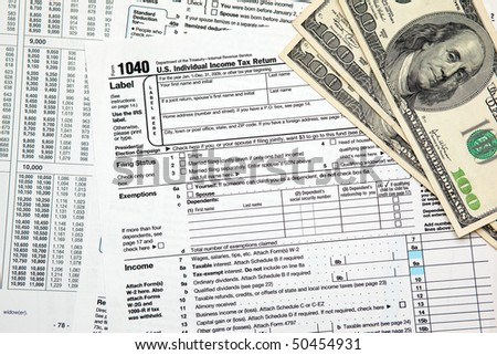 Tax time - Closeup of U.S. 1040 tax return with $100 bills - stock photo