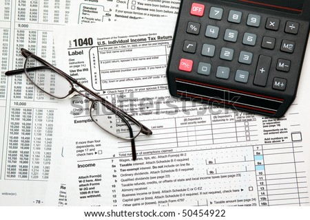 Tax time - Closeup of U.S. 1040 tax return with calculator and glasses