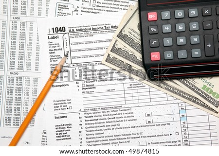 Tax time - Closeup of U.S. 1040 tax return with pencil and calculator - stock photo