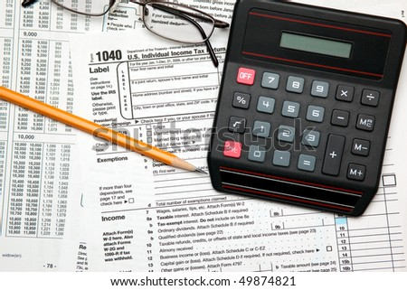 Tax time - Closeup of U.S. 1040 tax return with pencil, glasses and calculator - stock photo