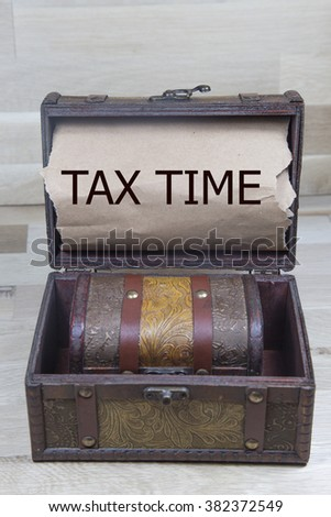 tax time is written on the Brown torn paper in the treasure box - stock photo