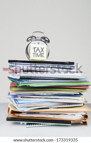 Tax time on an alarm clock face over the stack of documents - stock photo