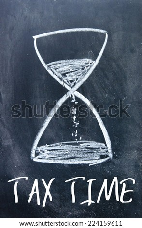 tax time text and hourglass sign on blackboard - stock photo