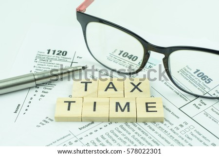 Tax Time text wooden block with on U.S. tax form