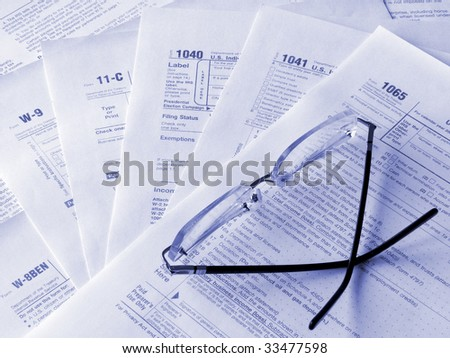 Taxes forms and glasses. Toned blue. Shallow DOF. - stock photo