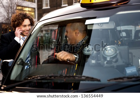 Taxi cab driver communicating with male passenger. - stock photo