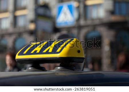 taxi cap on a car roof against the city - stock photo
