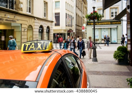 Taxi car waiting for passenger in the center of Luxembourg with people and touristis admiring the city - stock photo