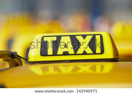 Taxi cars are waiting in row on the street - selective focus - stock photo