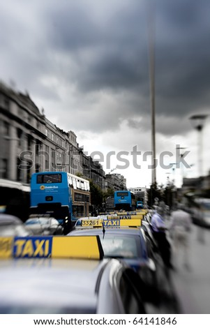 Taxi cars in Dublin, Ireland center symbol - spire with tilt and shift lens - stock photo