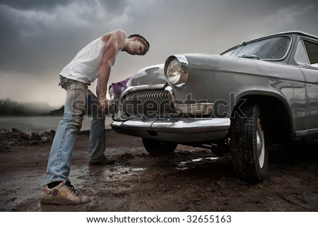 Taxi driver is trying to start his car manually. Cloudy skies and dirty wet road on the background. - stock photo