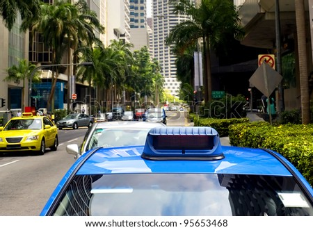 Taxi in the central sreet in Singapore. Sharpness on a blue car - stock photo