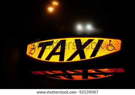 Taxi sign lit up showing the word Taxi and the disabled symbol - stock photo