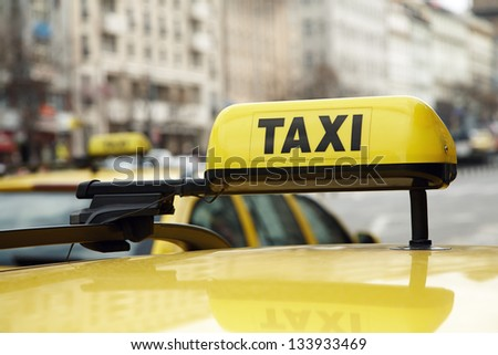 Taxi sign on a yellow car on urban street - stock photo