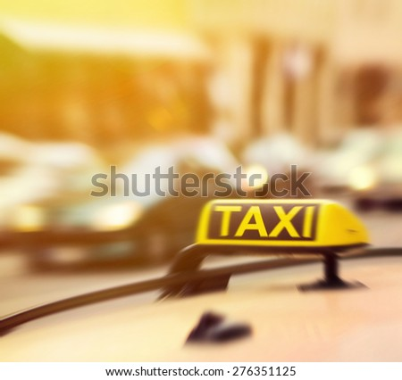 Taxi sign on car in motion blur - stock photo