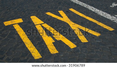 Taxi sign on cobblestones - stock photo
