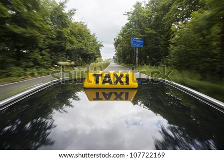 Taxi sign on top of a car, driving on a dual carriage way - stock photo