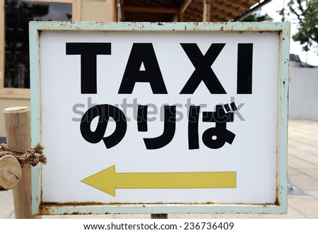Taxi sign with arrow and in Japanese and English language indicating the spot where the taxi stand is situated - stock photo