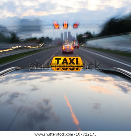 Taxi speeding over a motorway through the rush hour towards a large city - stock photo