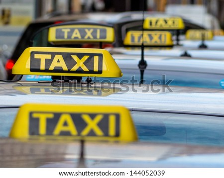 taxis wait at a taxi rank, symbol photo for passenger transport and services - stock photo