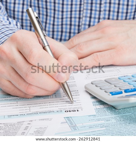 Taxpayer filling out 1040 Tax Form - stock photo