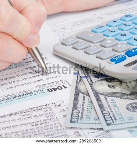 Taxpayer filling out USA 1040 Tax Form - studio shot - stock photo