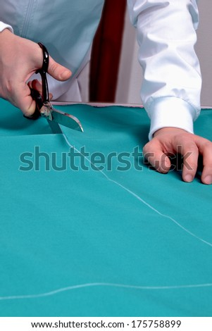 Taylor cutting fabric using a scissor.Cutting fabric with a taylor scissors - stock photo