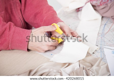 Taylor cutting fabric using a scissor.Cutting fabric with a taylor scissors