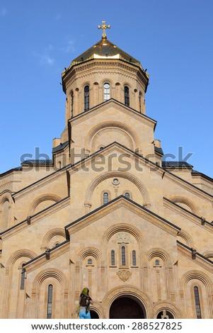 TBILISI, GEORGIA - JUNE 14, 2015: Holy Trinity cathedral, or Tsiminda Sameba, and a woman - stock photo