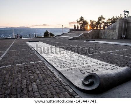 TBILISI, GEORGIA - JUNE 23: The Chronicle of Georgia (Stonehenge) in Tbilisi, Georgia, on June 23, 2013 at sunset. The Chronicle shows the history and religious believes of the country. - stock photo