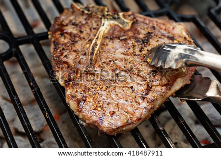 Tbone beef steak being cooked on a grill with tongs - stock photo
