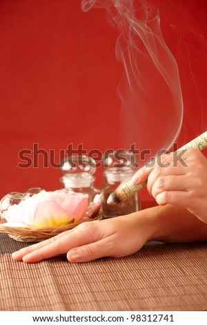TCM Traditional Chinese Medicine. Hand applying moxa stick therapy, natural herbs in glass jars in background - stock photo