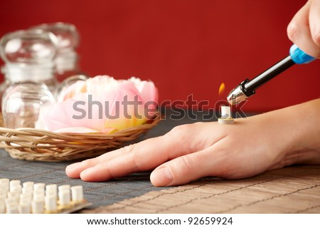 TCM Traditional Chinese Medicine. Hand lighting mini moxa stick, flower and natural herbs in glass jars in background. - stock photo