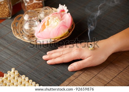 TCM Traditional Chinese Medicine. Smoking mini moxa stick, flower and natural herbs in glass jars in background. - stock photo
